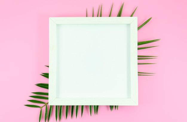 Cadre blanc plat à fond rose avec feuilles tropicales de palmier Photo Premium