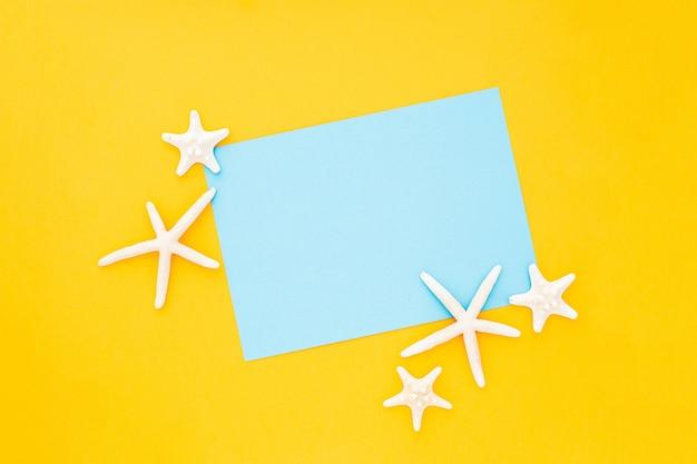 Cadre bleu avec des étoiles de mer autour sur fond jaune Photo gratuit