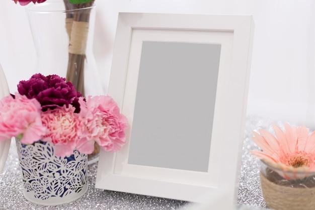 Cadre en bois blanc orné de fleurs et de feuilles Photo Premium