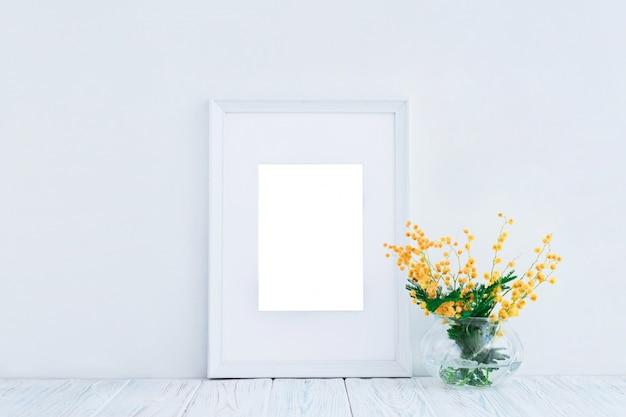 Cadre En Bois Blanc Vide Et Fleurs De Mimosa Jaune Avec Espace De Copie. Maquette. Photo Premium