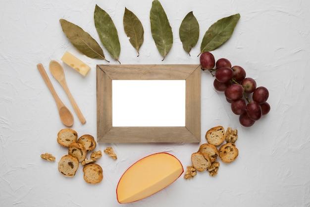 Cadre en bois vide entouré d'ingrédients savoureux Photo gratuit