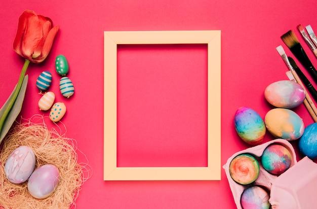 Un cadre de bordure jaune vide avec des oeufs de pâques colorés; pinceaux; tulipe sur fond rose Photo gratuit