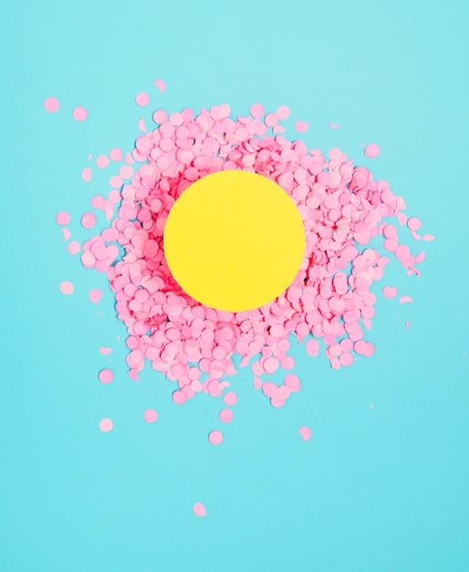Cadre De Cercle Blanc Jaune Au-dessus Des Petits Confettis Roses Festifs Sur Fond Bleu Photo gratuit