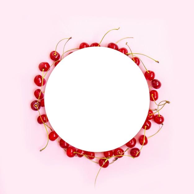Cadre de cercle de cerises mûres rouges à la menthe verte laisse sur un fond rose Photo Premium
