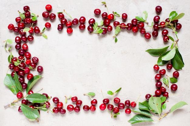 Cadre de cerises rouges mûres sur la table grise texturée Photo Premium