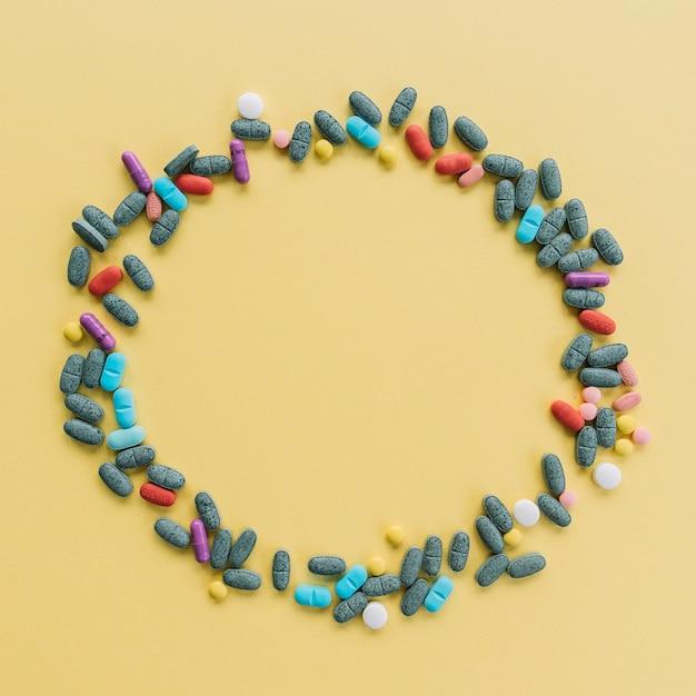 Cadre circulaire fait avec des pilules colorées sur fond jaune Photo gratuit