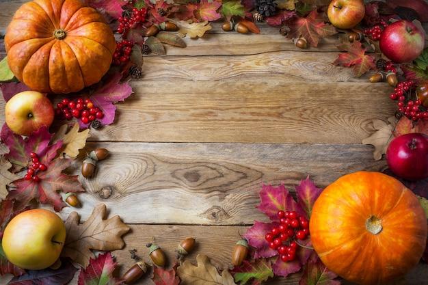Cadre de citrouilles, pommes, glands, baies et feuilles d'automne sur fond en bois Photo Premium