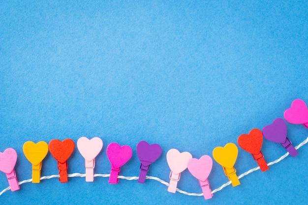 Un cadre de coeurs en bois colorés, suspendu à une corde sur un fond bleu. Photo Premium
