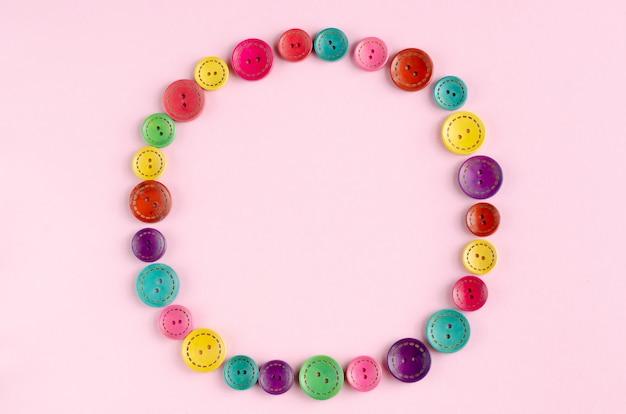 Cadre de composition de boutons de couture couleur sur fond rose. Photo Premium