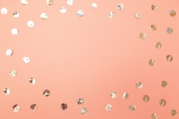 Cadre de confettis argent brillant sur fond de papier rose millénaire pastel. Photo Premium