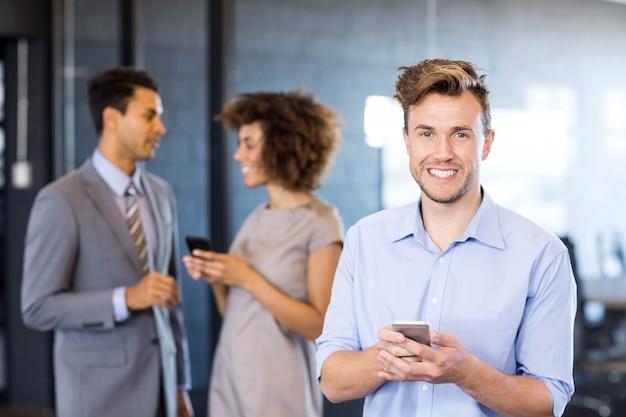 Cadre confiant utilisant son téléphone portable avec ses collègues de travailblack Photo Premium