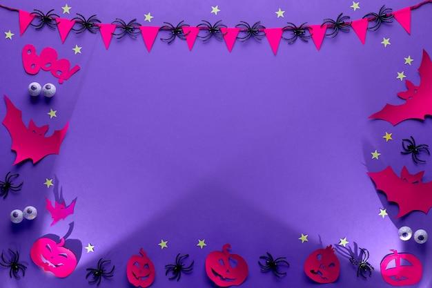 Cadre Créatif D'halloween En Violet, Rouge Et Noir, Mise à Plat Avec Copie-espace. Yeux En Chocolat, Figurines En Papier De Chauves-souris, Citrouilles Jack Lanterne, étoiles Et Guirlande Avec Drapeaux Et Araignées. Photo Premium