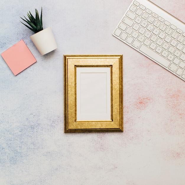 Cadre doré sur un bureau Photo gratuit