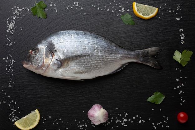 Cadre avec du poisson frais et des condiments Photo gratuit