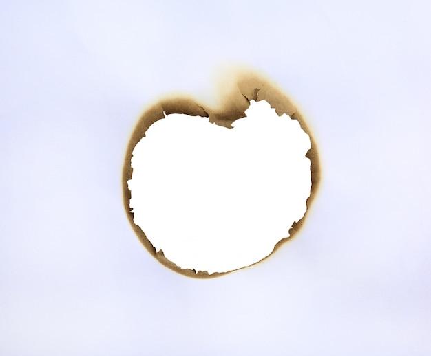 Cadre du trou brûlé dans du papier blanc. Photo Premium