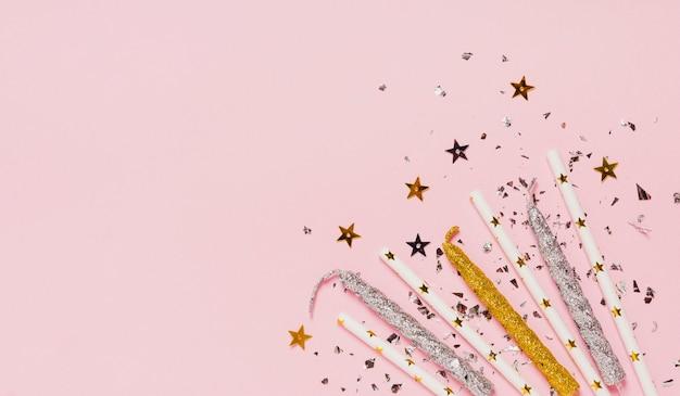 Cadre d'espace de copie vue de dessus avec des bougies et des paillettes sur fond rose Photo gratuit