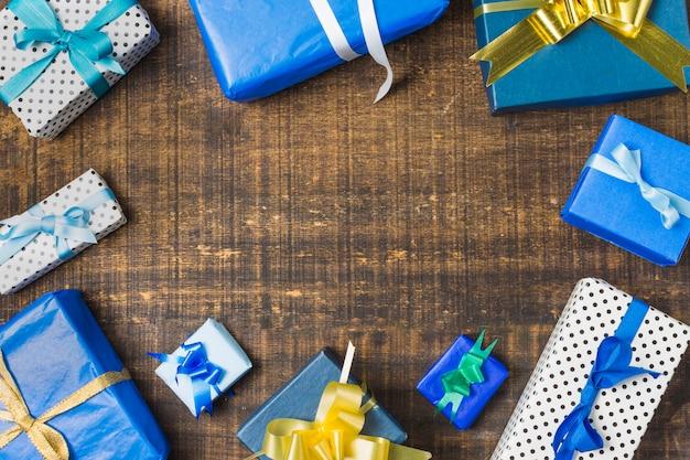 Cadre fabriqué avec des coffrets cadeaux emballés sur un bureau texturé Photo gratuit