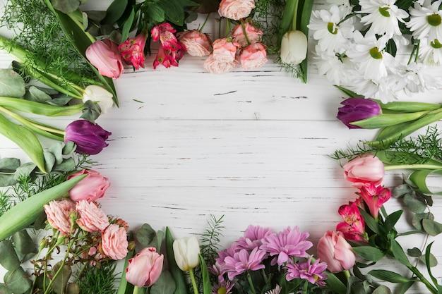 Cadre fabriqué avec différents types de belles fleurs sur une surface en bois Photo gratuit