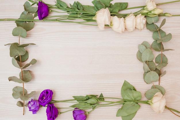 Cadre fait avec les fleurs d'eustoma blanc et violet sur fond en bois Photo gratuit