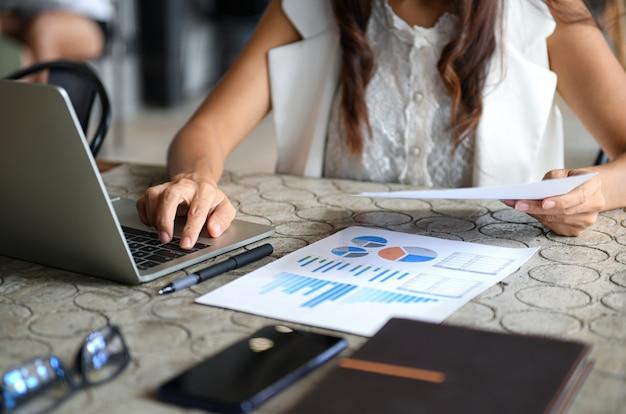 Un cadre féminin utilise un ordinateur portable et consulte le graphique de données de la société. Photo Premium
