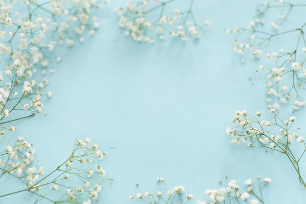 Cadre de fleurs de mariage sur fond bleu d'en haut. beau motif floral. style à plat Photo Premium