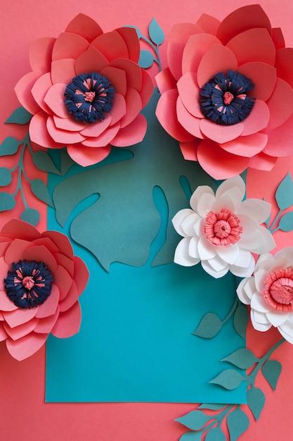 Cadre floral décoratif créatif de handcraft fait des fleurs en papier et des feuilles, carte pour l'invitation avec diverses feuilles sur un bleu. lay plat. Photo Premium