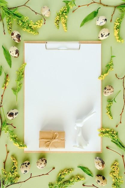 Cadre Floral De Printemps De Pâques Et Papier Vierge Blanc. Branches D'arbres Naturels, Fleurs Jaunes, œufs De Caille, Bloc-notes De Presse-papiers Sur Fond Vert Photo Premium