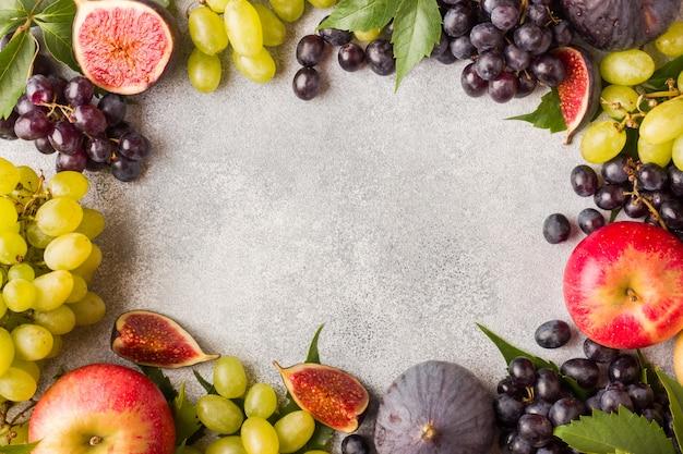 Cadre de fruits d'automne frais. raisins noirs et verts, figues et feuilles sur une table grise avec espace de copie. Photo Premium