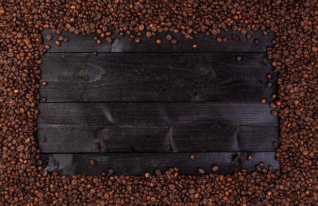 Cadre en grains de café torréfiés sur fond noir Photo Premium