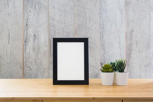 Un cadre d'image vide avec des plantes de cactus en pot Photo gratuit
