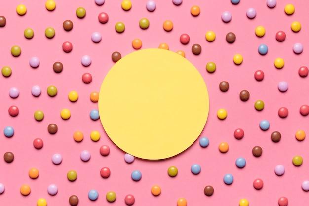 Cadre jaune circulaire sur les bonbons multicolores multicolores sur fond rose Photo gratuit