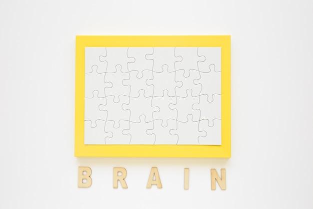Cadre jaune avec puzzle près de mot de cerveau Photo gratuit