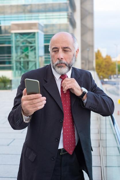 Cadre Mature Sérieux Avec Message De Lecture De Smartphone Photo gratuit