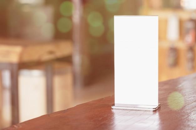 Cadre de menu debout sur une table en bois Photo gratuit