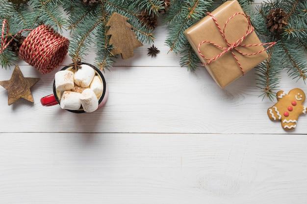 Cadre De Noël De Branches De Sapin, Jouets En Bois Et Tasse De Café Avec Guimauve Au Centre Sur Planche De Bois Blanc. Vue De Dessus. Photo Premium