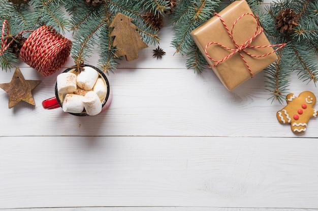Cadre De Noël De Branches De Sapin, Jouets En Bois Et Tasse De Café Avec Guimauve Sur Planche De Bois Blanc Photo Premium