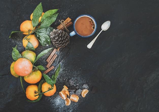 Cadre De Noël Ou Du Nouvel An. Mandarines Fraîches Avec Feuilles, Bâtons De Cannelle, Vanille, Pomme De Pin Et Tasse De Chocolat Chaud Sur Pierre Noire, Vue Du Dessus Photo Premium