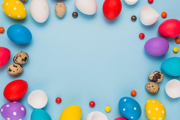 Cadre des oeufs de pâques et des bonbons sur la table bleue Photo gratuit