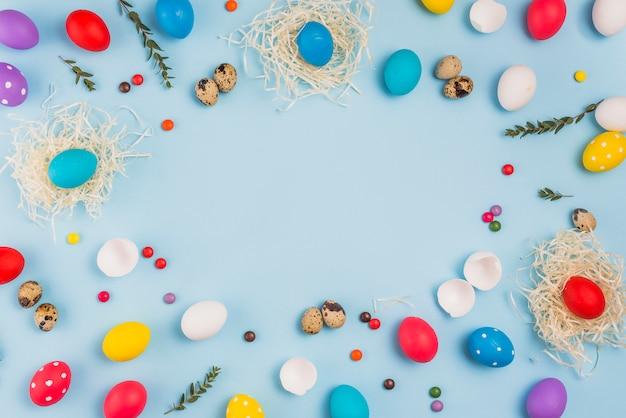 Cadre d'oeufs de pâques dans des nids et des bonbons Photo gratuit
