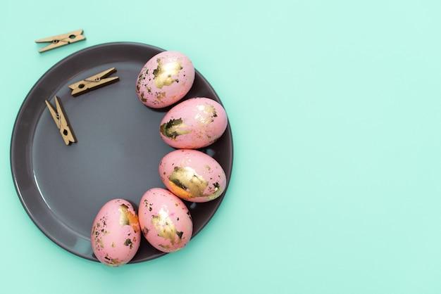 Cadre des oeufs de pâques doré décorés sur fond bleu pastel. Photo Premium