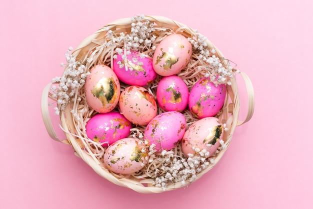 Cadre des oeufs de pâques doré décorés sur fond rose pastel. Photo Premium
