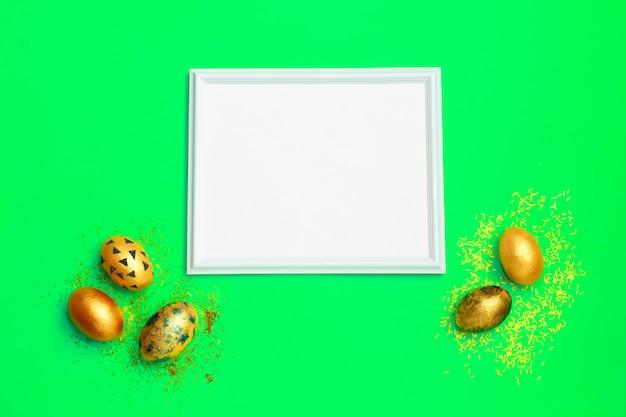 Cadre avec des oeufs de pâques tachetés d'or sur fond vert Photo Premium