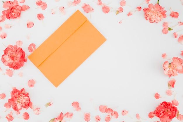 Cadre de pétales vue de dessus avec enveloppe Photo gratuit