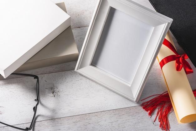 Cadre photo blanc blanc et matériel d'éducation ou de remise des diplômes sur une table blanche en bois Photo Premium