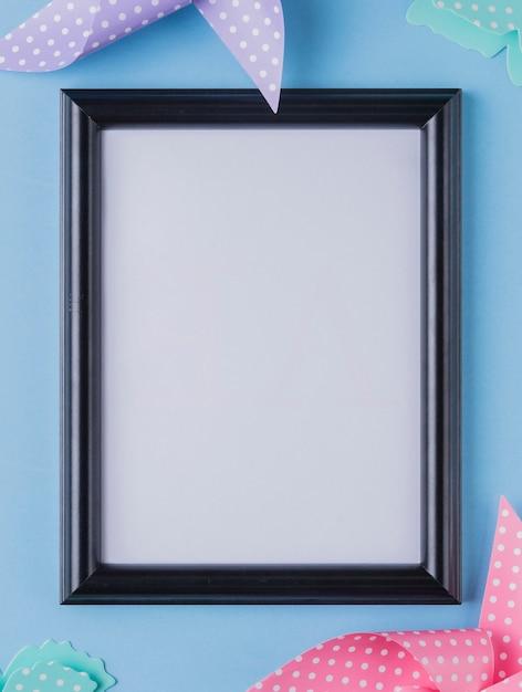 Cadre photo blanc entouré de papier origami Photo gratuit