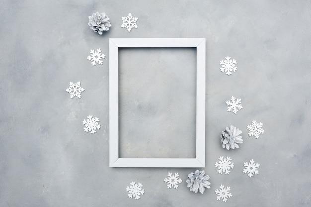 Cadre photo blanc avec fond. vacances . flocons de neige et cônes Photo Premium