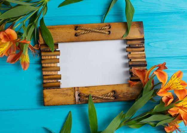 Cadre photo en bois sur bois bleu avec espace de copie de fleurs alstroemeria Photo Premium