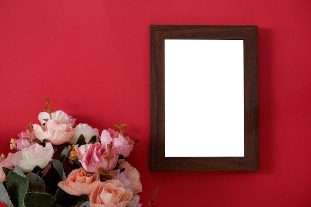 Cadre photo en bois maquette avec un espace pour le texte ou l'image sur fond rouge et fleur. Photo Premium