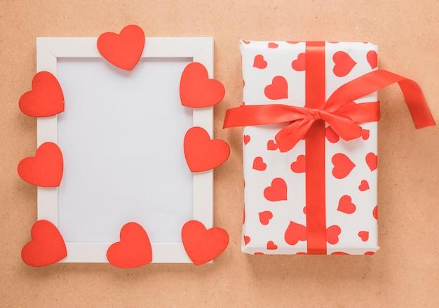 Cadre photo avec coeurs d'ornement près de la boîte présente Photo gratuit