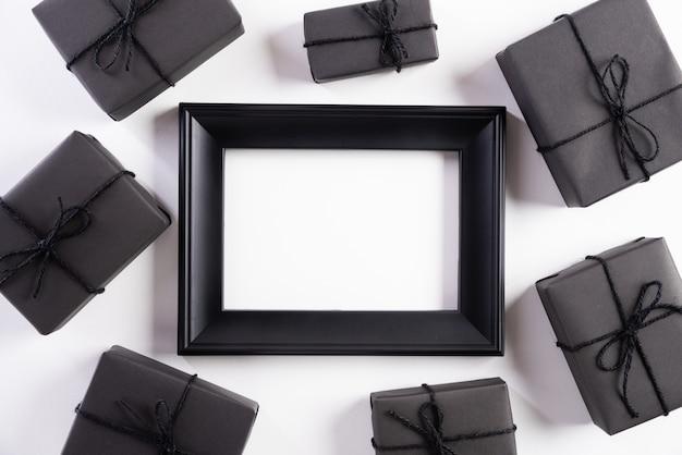 Cadre photo noir avec une boîte cadeau sur fond blanc. vendredi noir Photo Premium